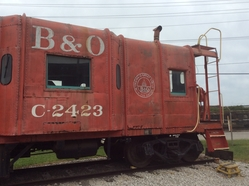 An ex-B&O caboose parked in front of the roundhouse